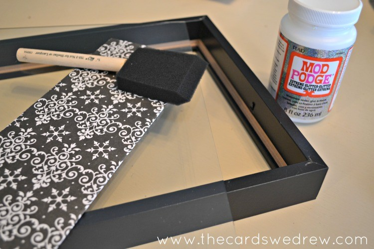 apply paper with mod podge to glass in frame