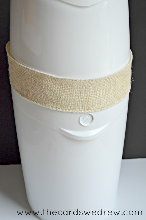 diaper genie pail with ribbon around it