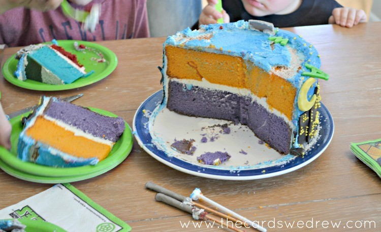 ninja turtle layered cake in orange purple red and blue